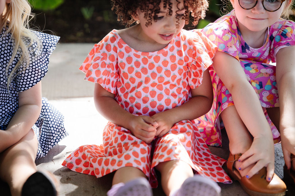 3 girls sitting in dot darling dress, strawberry dress, and ice cream dress
