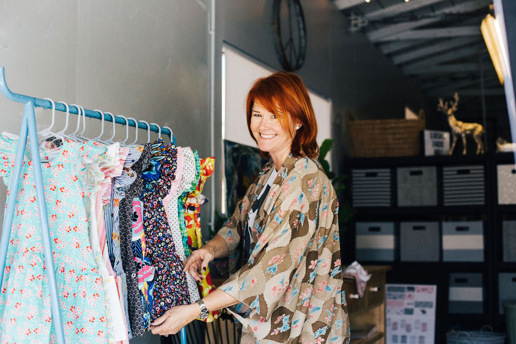 The founder of the company next to a rack of dresses  in the design studio