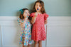 girls wearing strawberry and floral fruit dresses while eating lollipops against a blue wall
