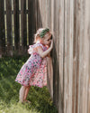girl wearing pink flower dress peeking through fence