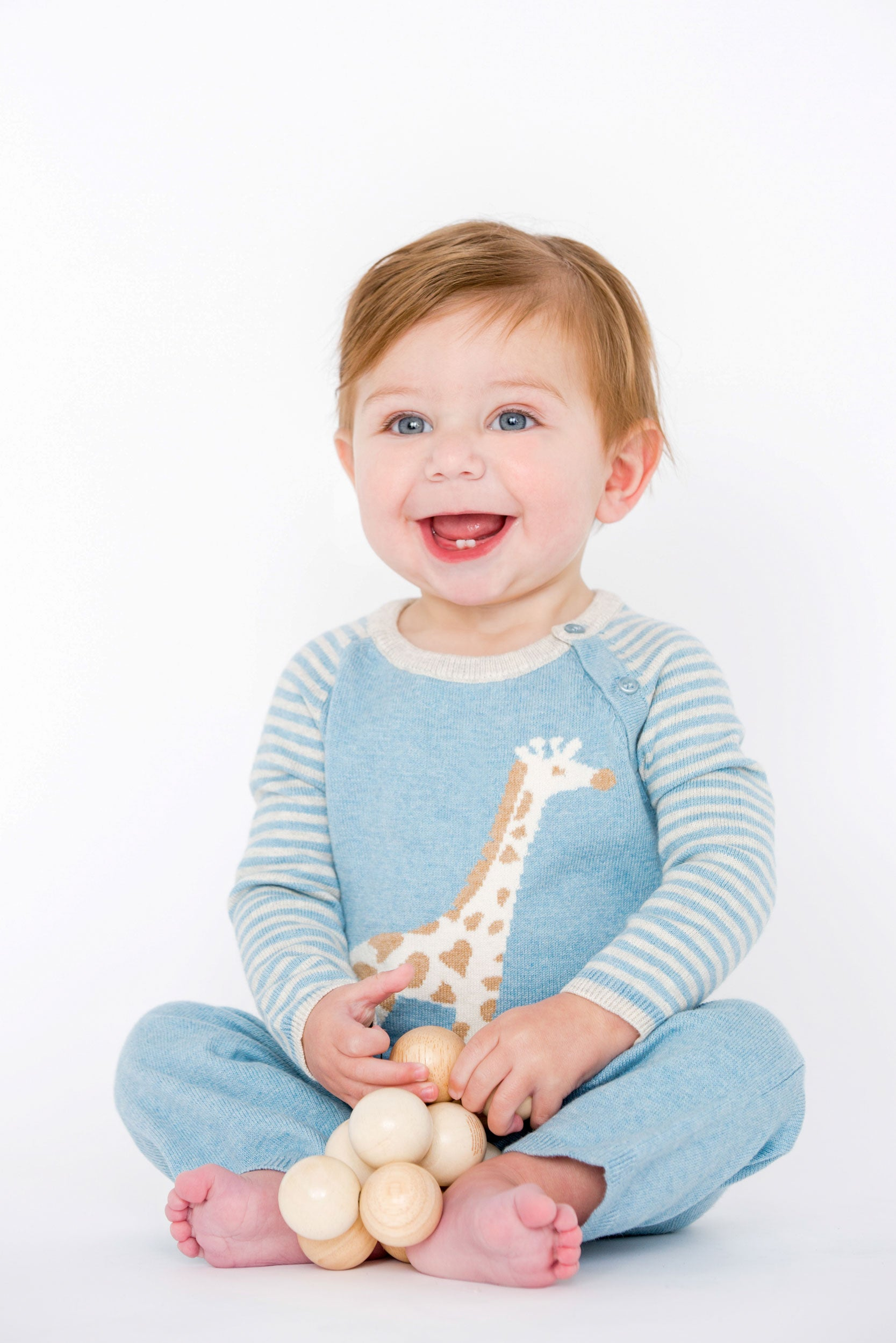baby  wearing blue giraffe coverall holding a wooden baby toy