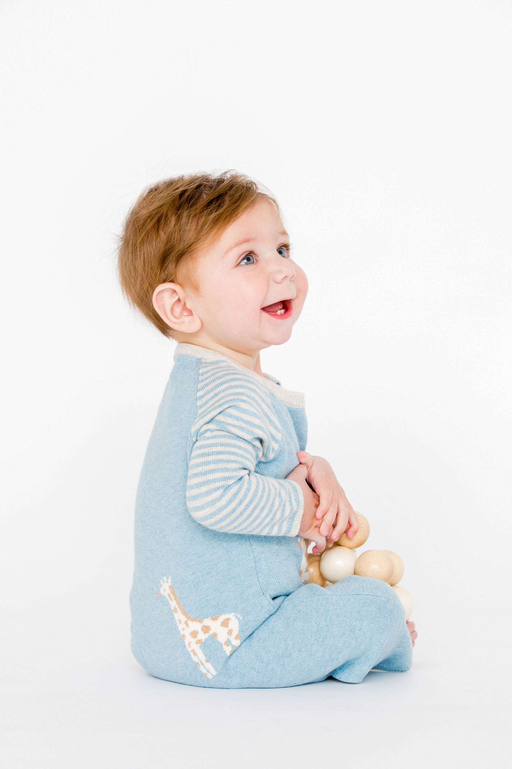 baby boy wearing blue giraffe coverall with back detail showing