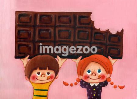 Two young children with a large chocolate bar.
