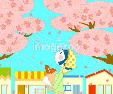 A young woman carrying loaves of bread under a row of blossom trees