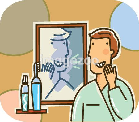 A man smiling at his reflection in the bathroom mirror while looking at his teeth
