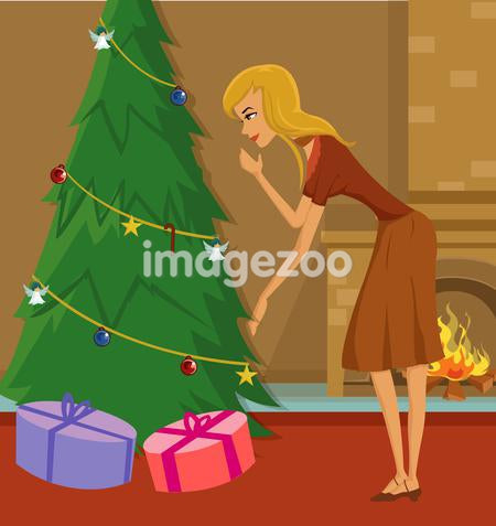 A woman placing gifts under a Christmas tree