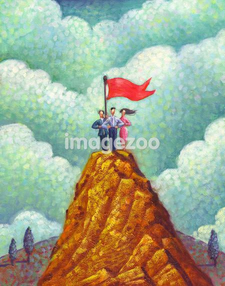 Three people and a flag on the peak of a mountain