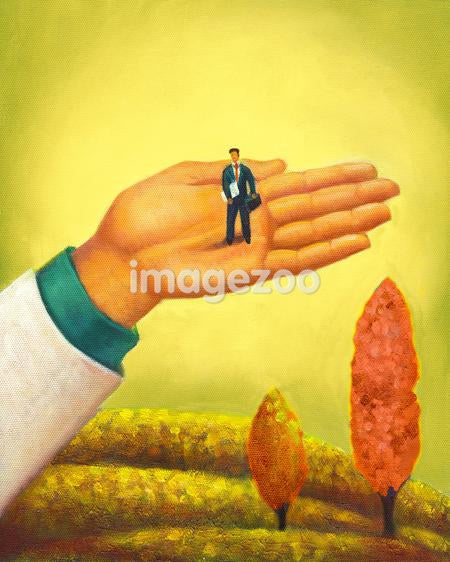 A businessman standing on a huge palm