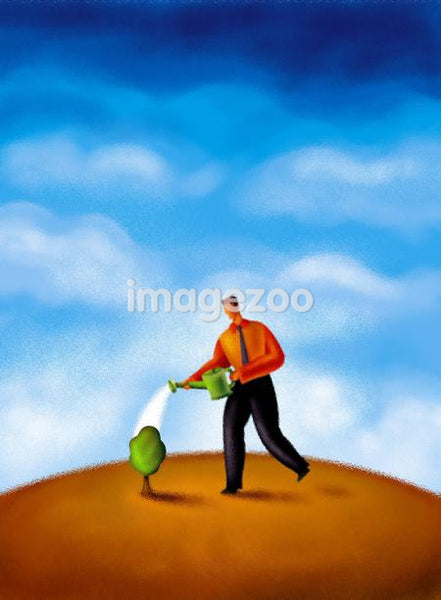 A man watering a small tree