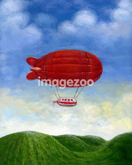 A red blimp floating over green hills