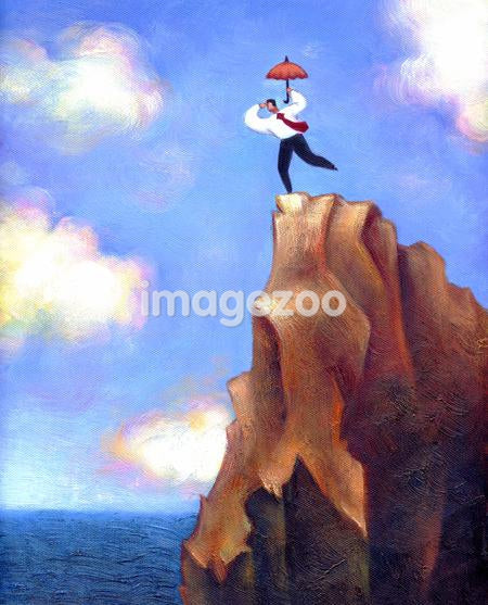 Businessman with umbrella looking down over the edge of a cliff