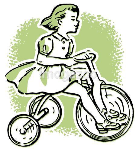 A young girl playing on a tricycle