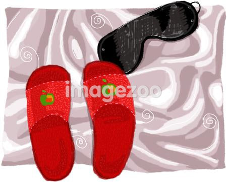 A pair of slippers and a sleeping mask on satin sheets