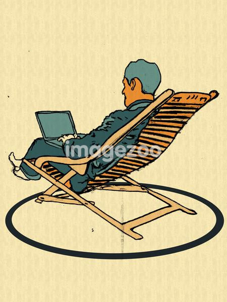 A businessman in a lounge chair using his laptop