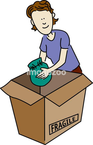 A woman placing a wrapped object into a box marked fragile