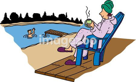 A woman having coffee in the morning watching a boy swim in a lake