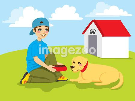 A boy setting down a dog bowl for his dog