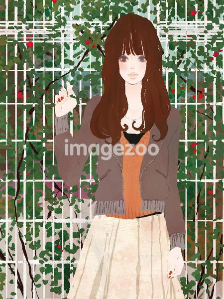 Young woman standing with fence and plant in background