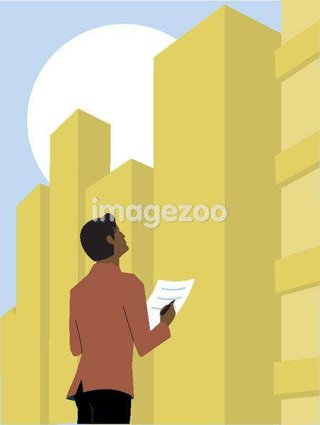 Man looking up at an office building and taking notes