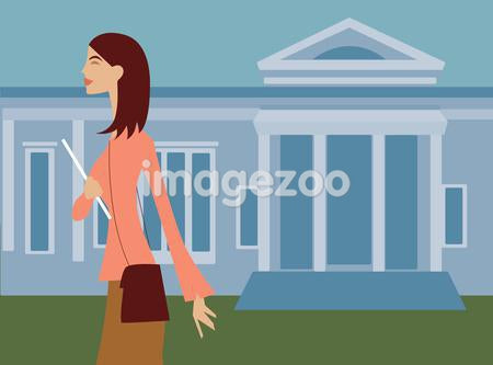 A woman walking with a notebook in front of an institutional style building