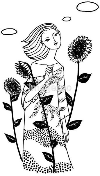 A woman standing in between sunflowers