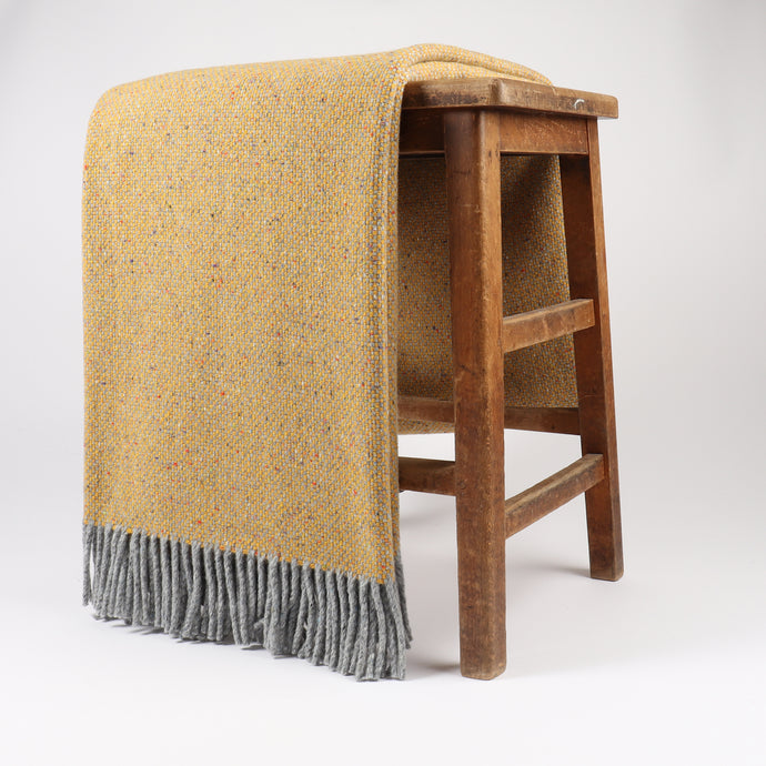 Maree has a soft, luxurious texture complimented by a hopsack design. Woven with 100% Merino Wool at the Bute Fabrics mill, featuring a traditional Donegal fleck throughout the fringed throw.