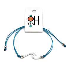 Wave Bracelet branded with O Yeah Gifts logo on hangtag. Bracelet is aqua blue with a silver wave charm and two beads.