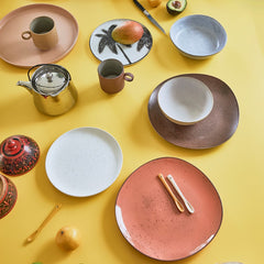 yellow table with peach, pink and orange colored ceramics