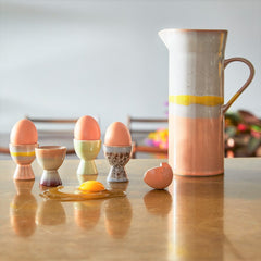 sunny breakfast table setting with egg cups and a ceramic jug in pastel colors