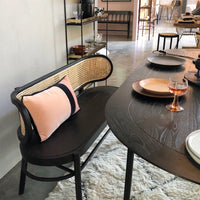 black wooden bench with cane webbing back and black dining table