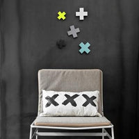 black wall with x shaped hooks in various colors