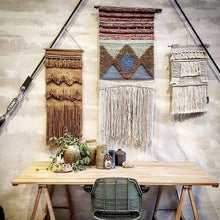 Trestle table used as desk with wall hanging rugs