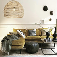 Velvet sofa in ochre color with large wicker lamp