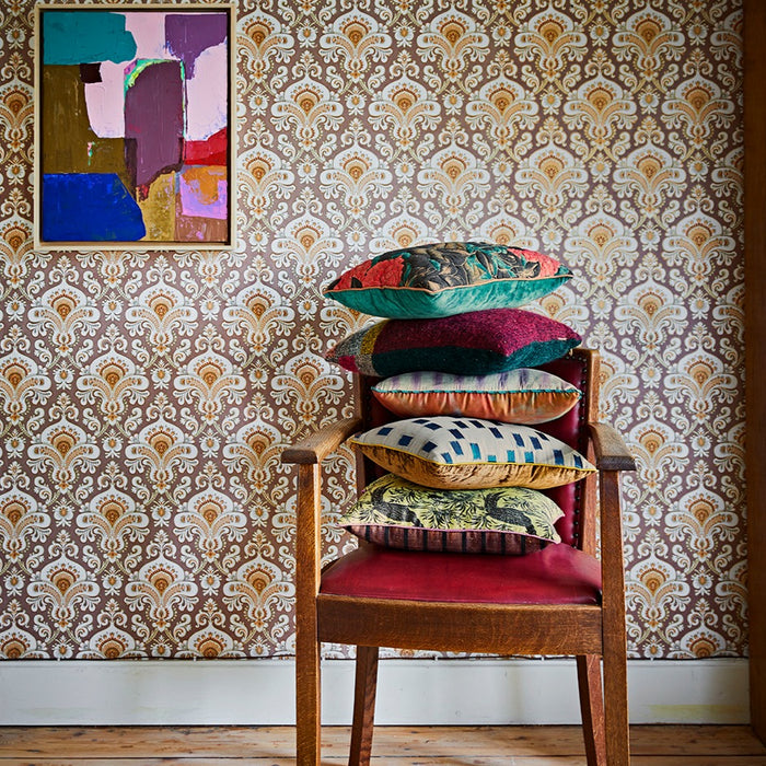 retro style wall paper in brown tones with a framed abstract painting in pink blue and green next to a chair with a pile of vintage inspired pillows