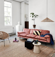 living room with velvet pink sofa and black mirror coffee table