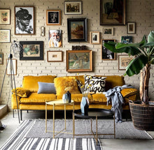 Family room with velvet ochre sofa and black and brass table