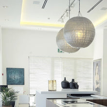open kitchen with two mother of pearl round chandeliers next to eachother