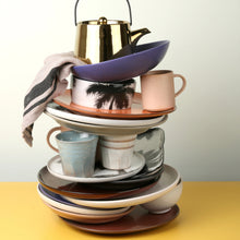 colorful stack of ceramic plates, bowls and mugs