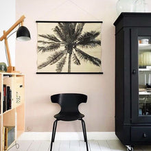 Living room with palm wall chart and black chair