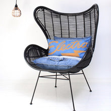 copper pendant light and black rattan egg chair with blue denim cushions
