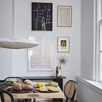 gallery wall in a dining room with white ufo pendant light