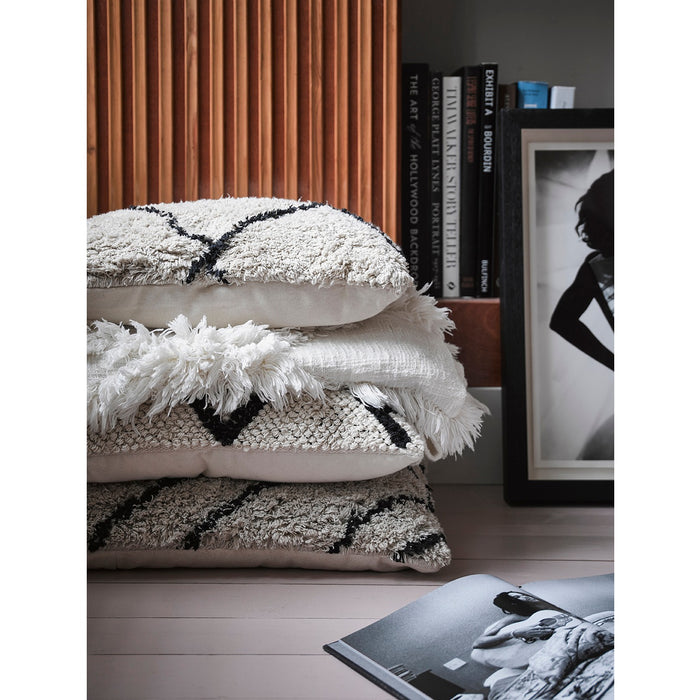 stack of pillows and blanket with fringes