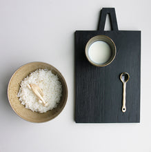 black cutting board and ceramic noodle bowl