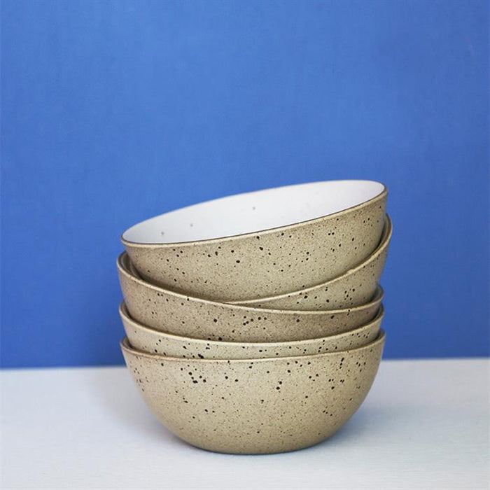 stack of ceramic egg shell bowls with a blue wall