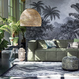 wicker basket light in a living room with green canvas couch, lots of plants and jungle image on wall
