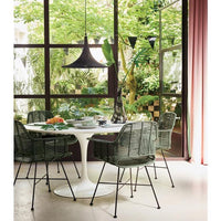 round dinner table with black pendant and green chairs