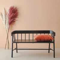 black wooden bench in shaker style in front of a peach colored wall