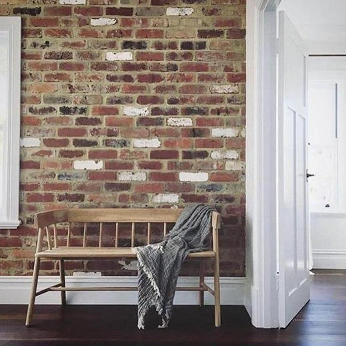 Wooden bench in loft setting with exposed brick and throw blanket