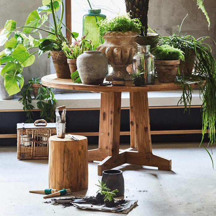 round teak table with flower pots and cement planter vase