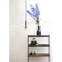 open shelf cabinet with black ceramic vase with handles and blue flowers